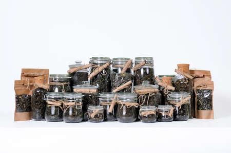 Various glass jars and gift packages of dry tea leaves of herbal aromatic tea on a white background