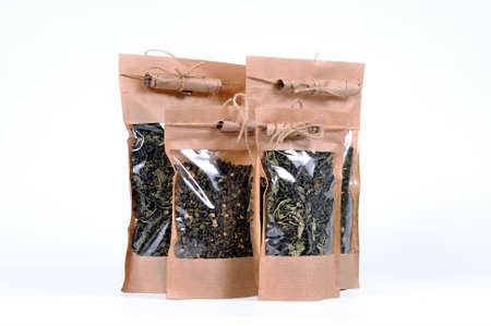 Dry tea leaves of herbal aromatic tea in a gift packages with transparent window on a white background