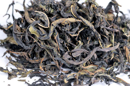 Dry tea leaves of herbal aromatic tea are scattered on a white background. Standard-Bild