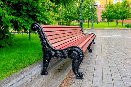 Bench in a city park on a rainy summer day against a lawn background with green grass, flowers and trees Standard-Bild