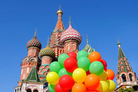 Saint St Basils Cathedral in Moscow on Red Square against a blue sky and with a bunch of colorful balloons in the foreground