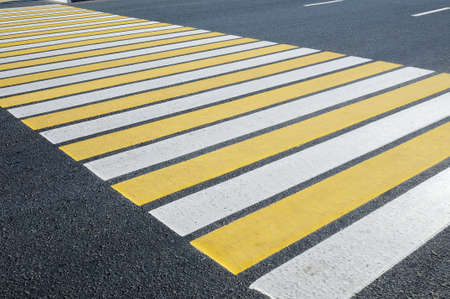 White and yellow strips of the crosswalk  pedestrian crossing through a street, without pedestrians. Perspective view.