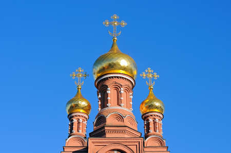 Gold domes and crosses of ancient Russian orthodox Christian church against the background of the blue sky