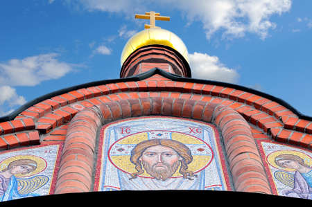 Gold dome, cross, icons from a mosaic with faces of Christ and Saints on ancient Russian orthodox Christian church