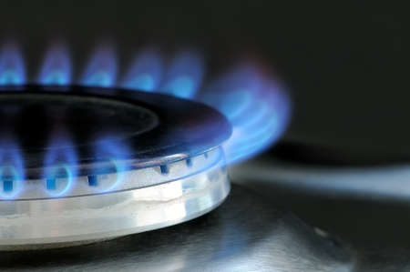 Natural gas burning on kitchen gas stove. Panel from steel with a gas ring burner on a black background, macro shooting Standard-Bild