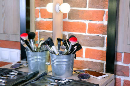 Professional brushes of the different sizes and forms for make up on a little table near a mirror and with sunglasses and the smartphone Standard-Bild