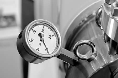 Pressure gauge on a blurry industrial background. Black and white toned image.