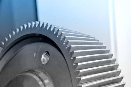 Part of an industrial cogwheel, gear. Blue toned image. Macro shooting