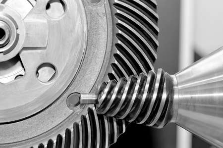 Industrial conical gear and a circular gear, cogwheel with spiral teeth. Black and white toned image. Macro shooting Standard-Bild
