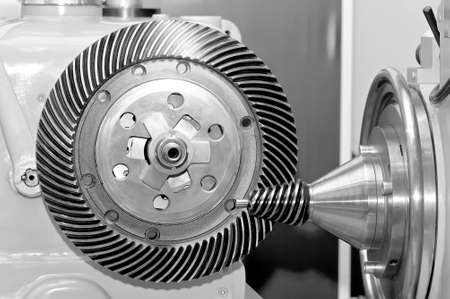 Industrial machine with a conical gear and a circular gear, cogwheel with spiral machine teeth. Black and white toned image Stock Photo
