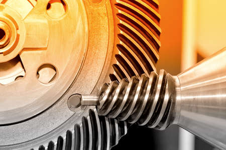 Industrial conical gear and a circular gear, cogwheel with spiral teeth. Red toned image. Macro shooting Standard-Bild