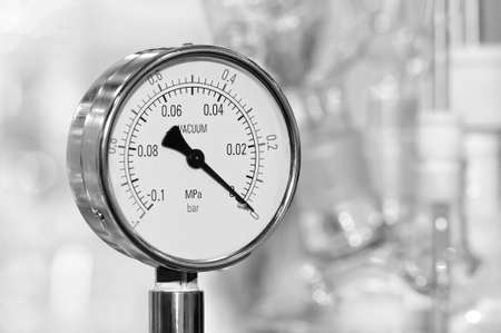 Pressure gauge on a blurry industrial background. Toned image.