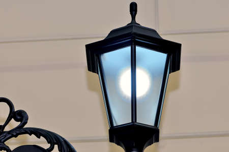 Plafond of a streetlight and element of a decorative fencing on a gray background