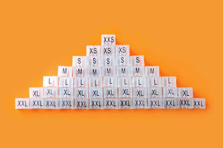 Various plastic clothing size tags, plastic size labels for hangers of clothing store with indexes of the XXS, XS, S, M, L, XL, XXL sizes on a orange background. Close up.