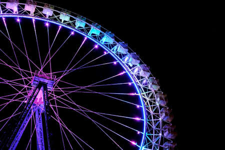 Big ferris wheel with festive purple and blue illumination against dark night sky. Side view.