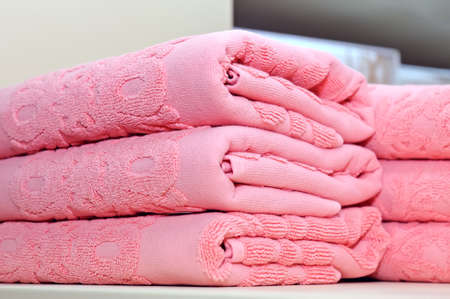 Pink terry towels are folded by a pile on the shelf.