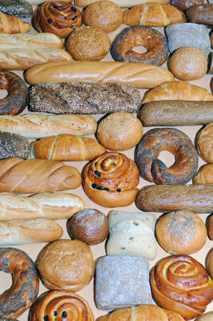 Assortment bakery products - bread long loafs, cakes, biscuits, cinnamon rolls as a background Stock Photo