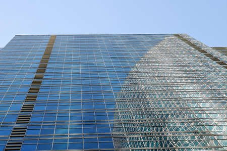 Wall of a modern skyscraper with windows on a facade and specular reflection in windows Stock Photo