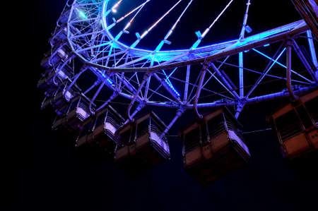 Big ferris wheel with festive blue illumination against night sky. Bottom view.