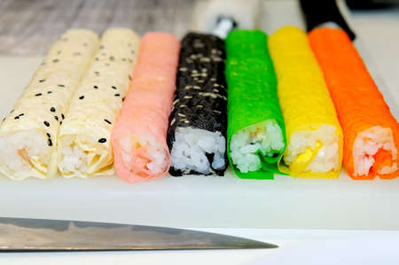Sushi rolls in tubes not yet cut into portions. Traditional japanese sushi with rice of different colors 写真素材