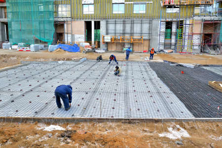 Construction site of apartment houses. Construction workers doing on a iron reinforcement and concrete foundation
