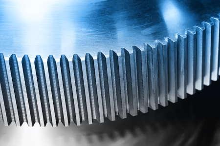 Industrial cogwheel, gear with machine teeth. Blue toned image. Macro shooting