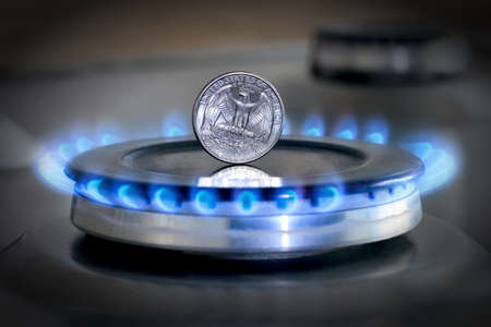 Gas hob with burning natural gas and quarter US dollar coin. The concept of the struggle for global gas markets. Turk stream. North stream Stock Photo