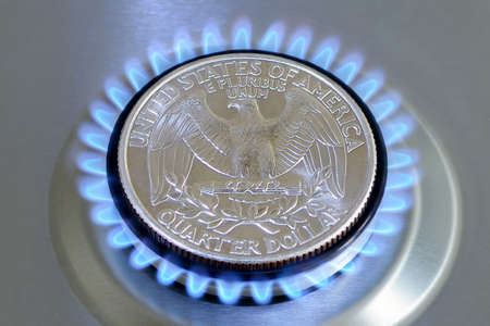Gas hob with burning natural gas and quarter US dollar coin. The concept of the struggle for global gas markets. Turk stream. North stream 版權商用圖片