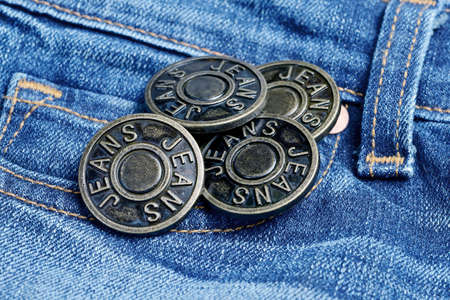 Metal buttons with inscription Jeans on a denim.