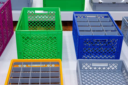 Plastic crates boxes of various colors and sizes. Plastic containers, backets Stock Photo
