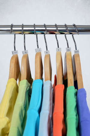 T-shirts of different colors hang on closing rack on wooden hangers with plastic size tags