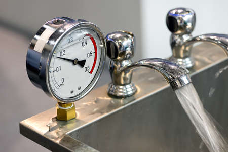 Hydraulic pressure gauges, manometers and water taps with water flowing from taps