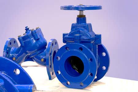 Válvulas industriales azules. Válvula de compuerta de cuña para tubería industrial. Válvula de mariposa con reductor. Válvula manual Foto de archivo