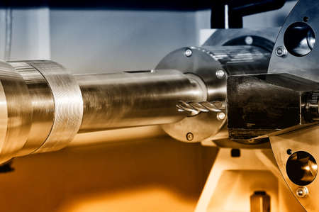 Metal billet is machined on an industrial milling machine. Brown toned image. Close up