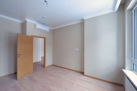 Empty room after repairs in an apartment building. Fresh renovated room with wooden floor Stock Photo