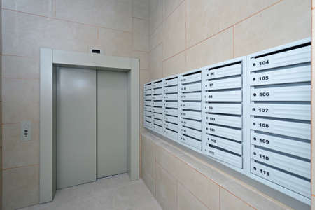 A lot of new mailboxes in the lobby of a residential building near the elevator