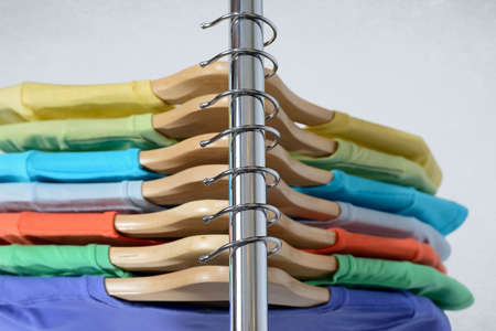 T-shirts of different colors hang on closing rack on wooden hangers on light Stock Photo