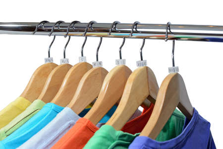 T-shirts of different colors hang on closing rack on wooden hangers with plastic size tags indexes of the XXS, XS, S, M, L, XL, XXL are isolated on white