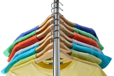 T-shirts of different colors hang on closing rack on wooden hangers are isolated on white