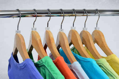 T-shirts of different colors hang on closing rack on wooden hangers with plastic size tags indexes of the XXS, XS, S, M, L, XL, XXL on a light Stock Photo
