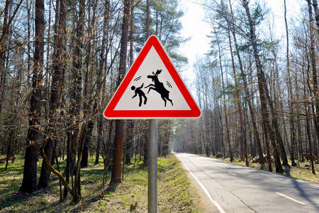 Warning road sign of a possible attack by wild elks on humans.
