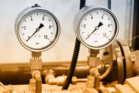 Hydraulic pressure gauges, manometers - instruments for measuring the pressure of fluid on a hydraulic equipment. Brown toned