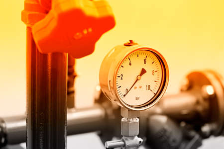 Hydraulic pressure gauge, manometer - instrument for measuring the pressure of fluid on a hydraulic equipment. Red toned Stock Photo