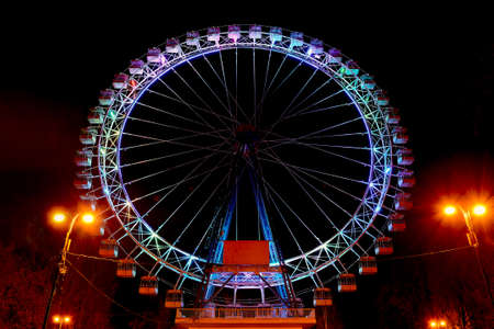 Ferris wheel in a night amusement park. Entertainment in the park Editorial