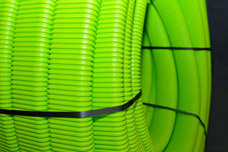 Green plastic corrugated tubes for water supply, rolled up. Shallow depth of field Stock Photo