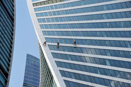 Industrial climbers washes the glass on the facade of a skyscraper.