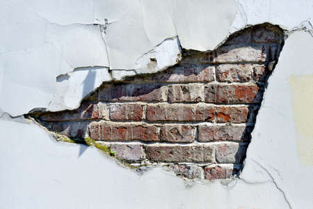 Old brick wall with destroyed plaster. Part of the plaster has fallen off, red bricks are visible from under the plaster.