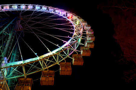 Part of ferris wheel with multicolor lighting against a night blue sky