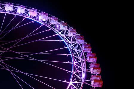 Part of ferris wheel with purple lighting  against a night dark sky Stok Fotoğraf