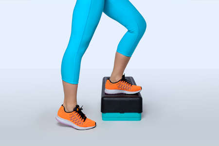 Woman in orange sneakers and turquoise sportswear do exercise on a black-turquoise aerobic and fitness step. 版權商用圖片